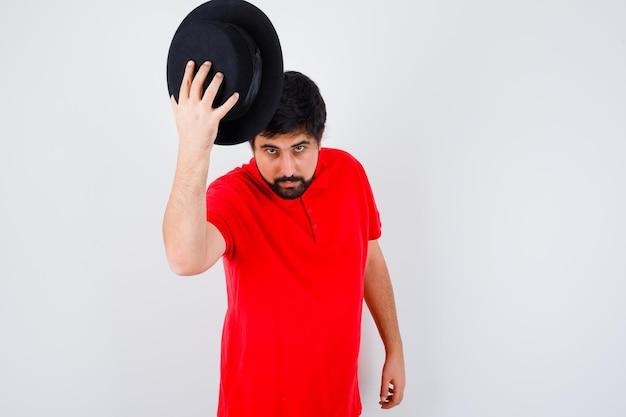 Jonge man die zijn hoed afdoet tijdens een ontmoeting met iemand in een rood t-shirt, zwarte hoed, vooraanzicht.
