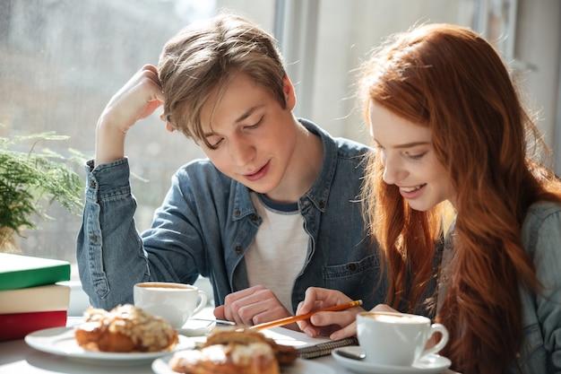 Jonge man die zijn jonge vrouw bekijkt die huiswerk doet