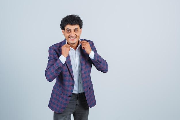 Jonge man die zijn kraag in shirt, jas, broek houdt en er knap uitziet. vooraanzicht.
