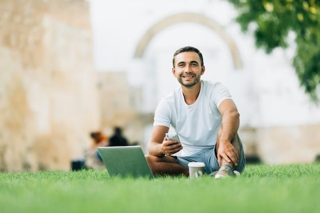 Jonge man die zijn laptop met koffie gebruikt om op het gras te gaan werken