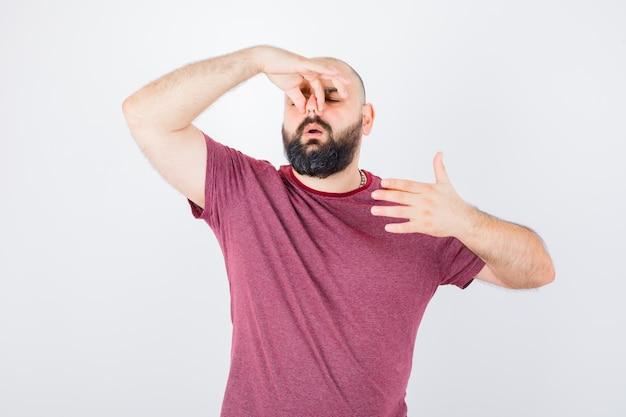 Jonge man die zijn linkerhand op de elleboog houdt, aan iets denkt in een roze t-shirt en er geïrriteerd uitziet, vooraanzicht.