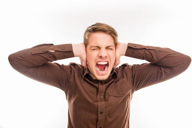 Jonge man die zijn oren bedekt en schreeuwt