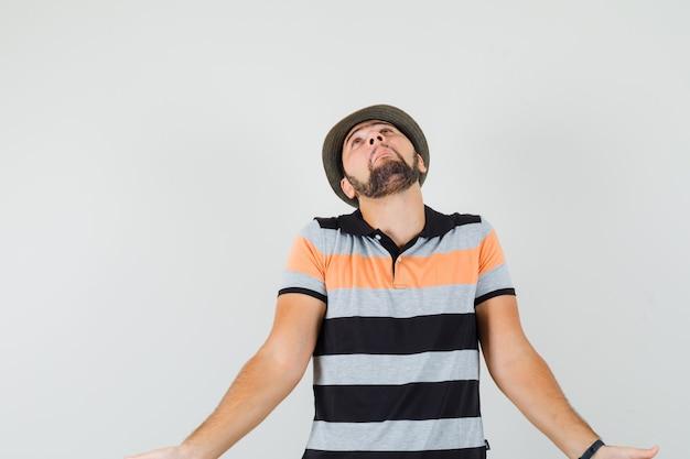 Jonge man die zijn schouders ophaalt terwijl hij in t-shirt, hoed omhoog kijkt en hulpeloos kijkt