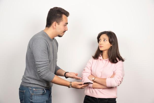Jonge man die zijn telefoon toont aan vrouw.