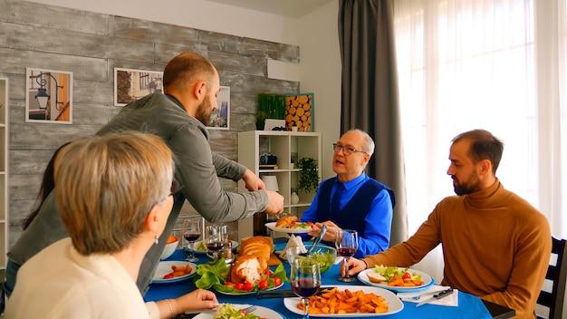 Jonge man die zijn vader serveert met een groot stuk kip tijdens het diner.
