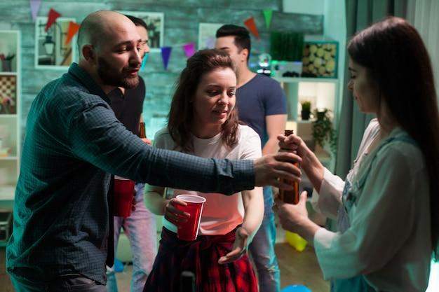 Jonge man die zijn vriendin een biertje geeft op een feestje met hun vrienden.