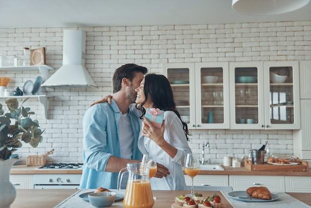 Jonge man die zijn vriendin een cadeau geeft terwijl hij samen aan het ontbijten is in de huishoudelijke keuken