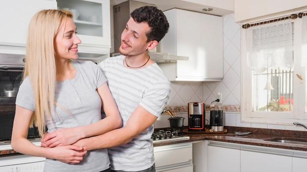 Jonge man die zijn vriendin omhelst die elkaar in de keuken bekijkt
