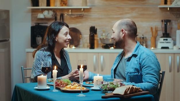Jonge man die zijn vriendin voorstelt tijdens een romantisch diner, in de keuken, zittend aan tafel en drinkt een glas rode wijn. verrast verloofde viering verloofde gelukkige vrouw die lacht