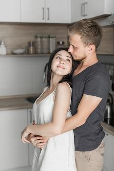 Jonge man die zijn vrouw omhelst die zich in de keuken bevindt