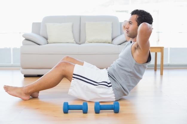 Jonge man doen abdominale crunches in de woonkamer
