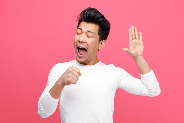 Jonge man doet alsof hij microfoon vasthoudt en hand in de lucht houdt terwijl hij met gesloten ogen zingt