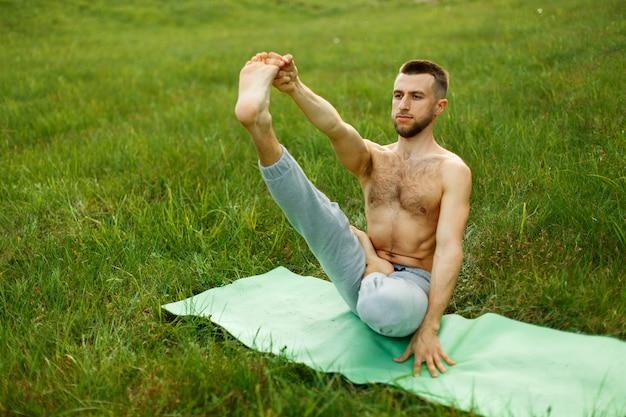 Jonge man doet de boot pose tijdens yoga praktijk in het park