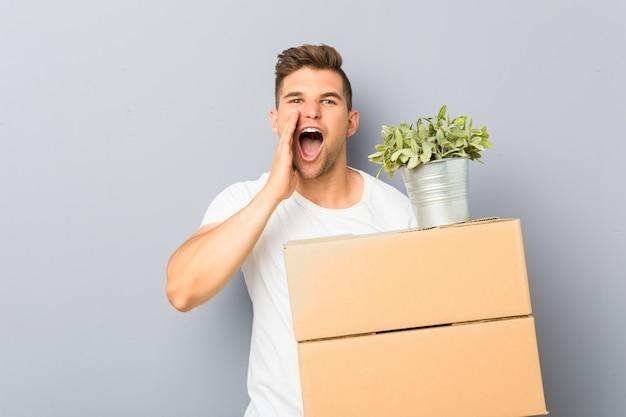 Jonge man doet een beweging houden dozen schreeuwen opgewonden naar voren