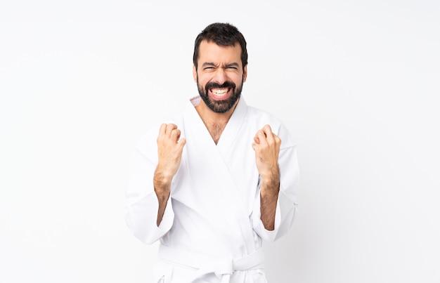 Jonge man doet karate over geïsoleerde witte muur gefrustreerd door een slechte situatie