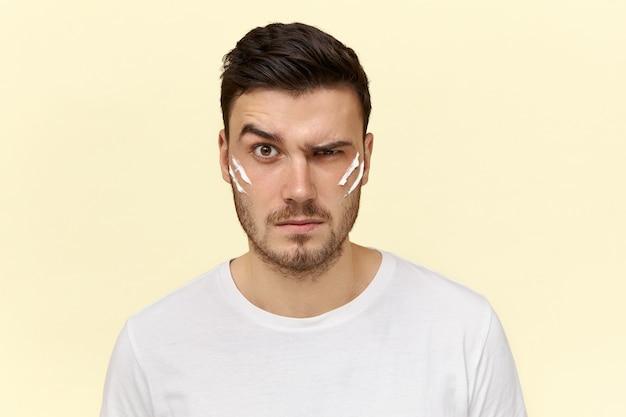 Jonge man doet ochtendroutine met lotioncrème op zijn gezicht
