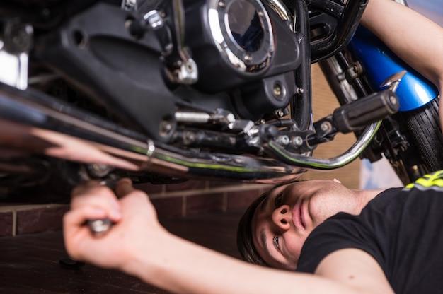 Jonge man doet onderhoud aan zijn motor, liggend op de vloer eronder met een sleutel in zijn hand, close-up