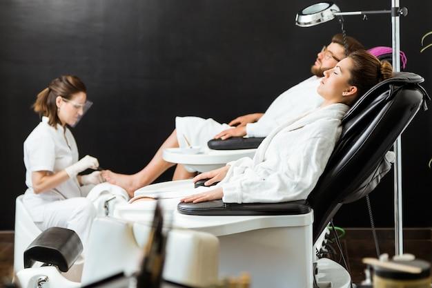 Jonge man doet pedicure in salon. schoonheidsconcept.