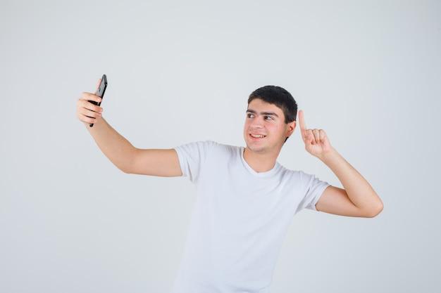 Jonge man doet selfie terwijl hij omhoog in t-shirt wijst en vrolijk, vooraanzicht kijkt.