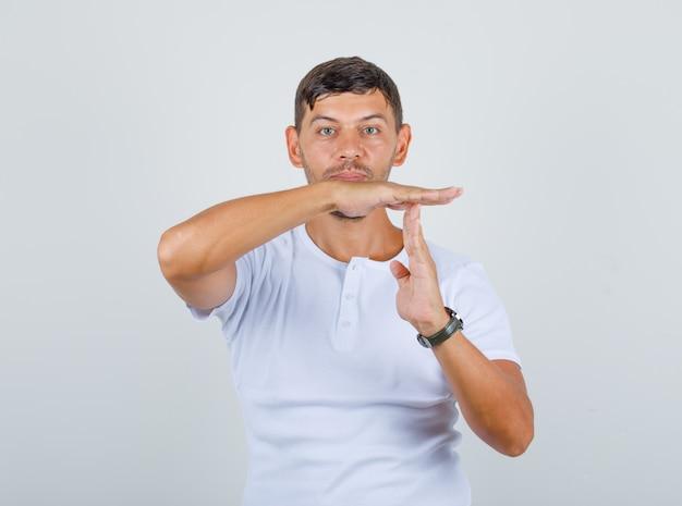 Jonge man doet tijdonderbreking gebaar in wit t-shirt, vooraanzicht.