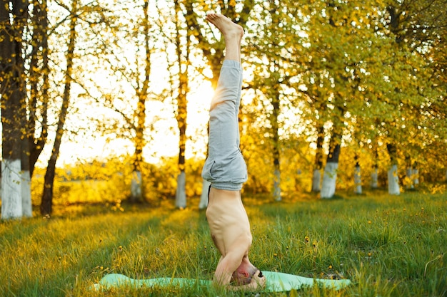 Jonge man doet yoga in het park bij zonsondergang. gezonde levensstijl