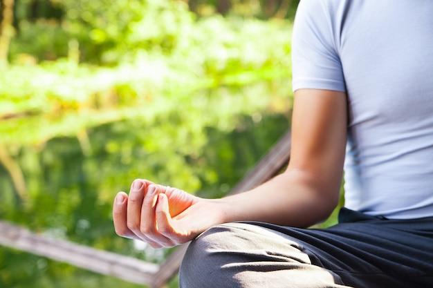 Jonge man doet yoga lotus pose in park