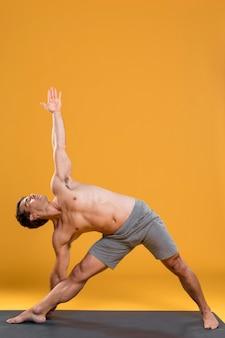 Jonge man doet yoga op mat