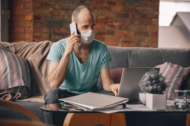 Jonge man doet yoga thuis terwijl hij in quarantaine en freelance werkt