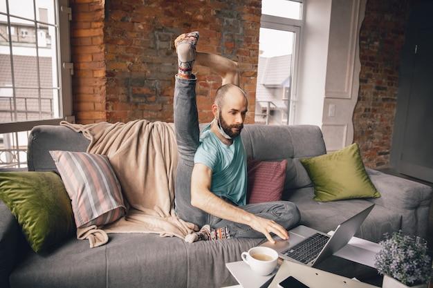 Jonge man doet yoga thuis terwijl hij in quarantaine is en freelance online werkt