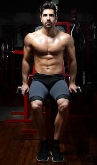 Jonge man doet zwaargewicht oefening in de sportschool.