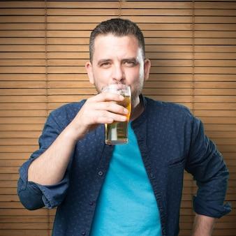 Jonge man draagt een blauwe outfit. bier drinken.