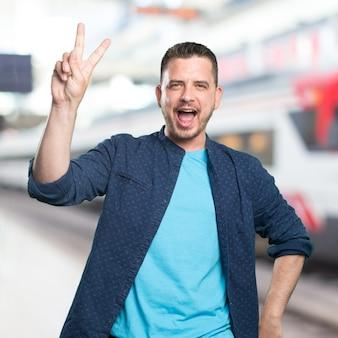 Jonge man draagt een blauwe outfit. doen overwinning gebaar.