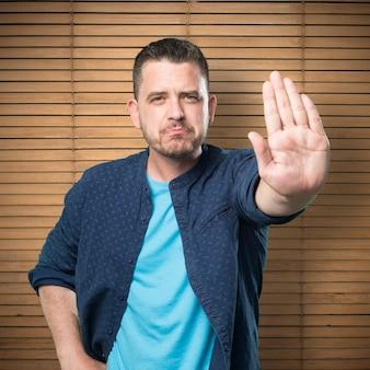 Jonge man draagt een blauwe outfit. doen stop gebaar.