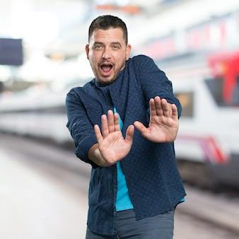 Jonge man draagt een blauwe outfit. op zoek bang.