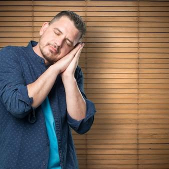 Jonge man draagt een blauwe outfit. op zoek slaperig.