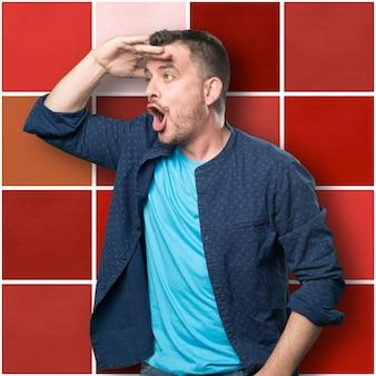 Jonge man draagt een blauwe outfit. op zoek verrast.