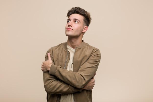 Jonge man draagt een bruine jas knuffels zichzelf, zorgeloos en gelukkig glimlachen