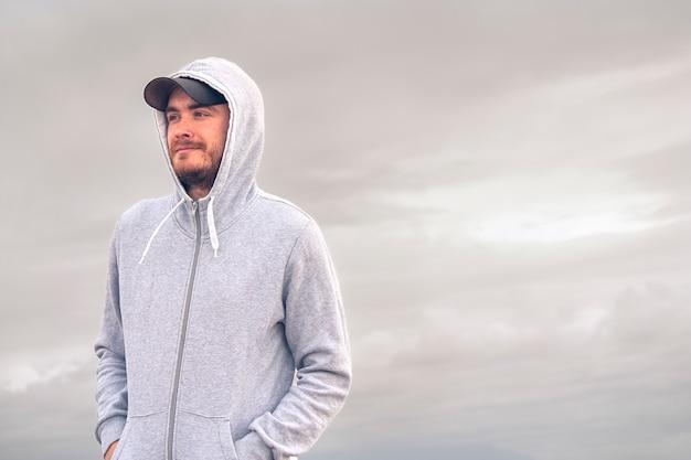 Jonge man draagt een hoodie en een baseball cap met een bewolkte dag achtergrond