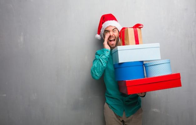 Jonge man draagt een kerstmuts met geschenken schreeuwen iets blij naar de voorkant