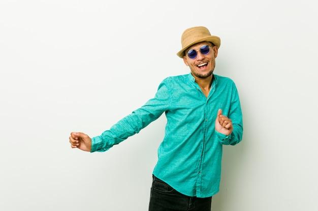 Jonge man draagt een zomer kleding dansen en plezier