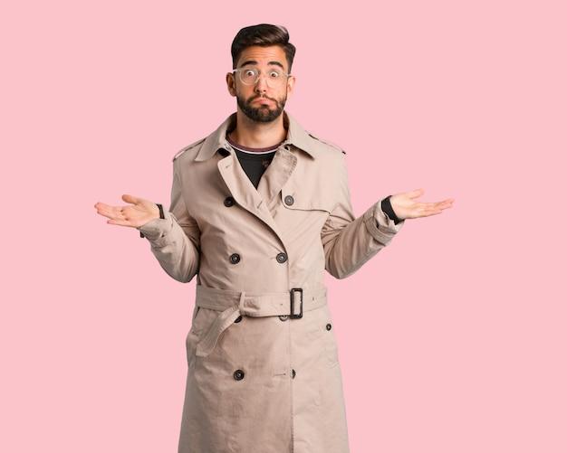 Jonge man draagt trenchcoat verward en twijfelachtig