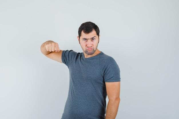 Jonge man dreigt met vuist in grijs t-shirt en nerveus op zoek