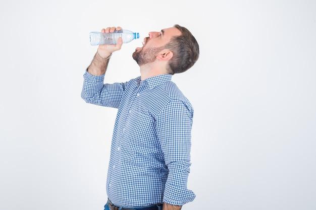 Jonge man drinken uit plastic waterfles in shirt, spijkerbroek en op zoek opgetogen, vooraanzicht.