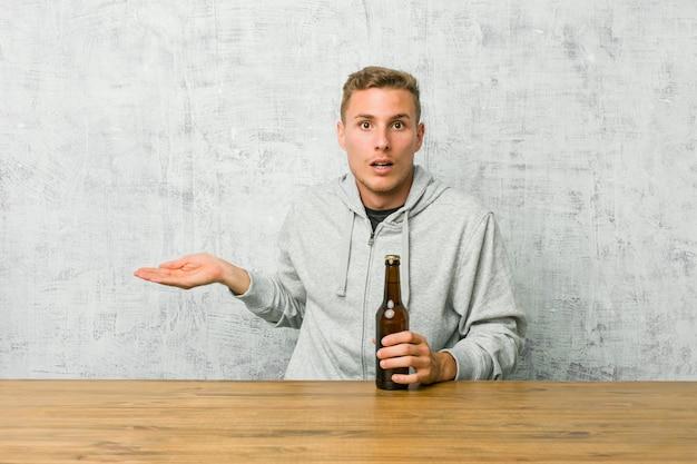Jonge man drinken van een biertje op een tafel onder de indruk kopie ruimte op palm te houden.