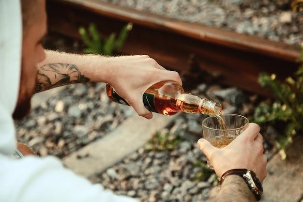 Jonge man drinkt alcohol op een verlaten spoorlijn op het platteland bij zonsondergang. concept van verdriet, apathie, depressie of een onjuiste levensstijl. ruimte kopiëren