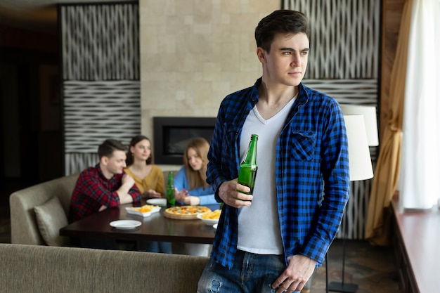 Jonge man drinkt bier uit een fles en kijkt uit het raam in een café