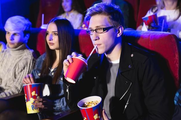 Jonge man drinkt uit beker in de bioscoop