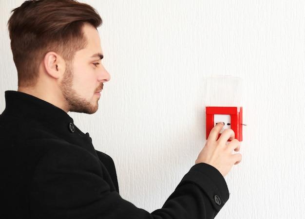 Jonge man drukknop van brandalarmsysteem, binnenshuis