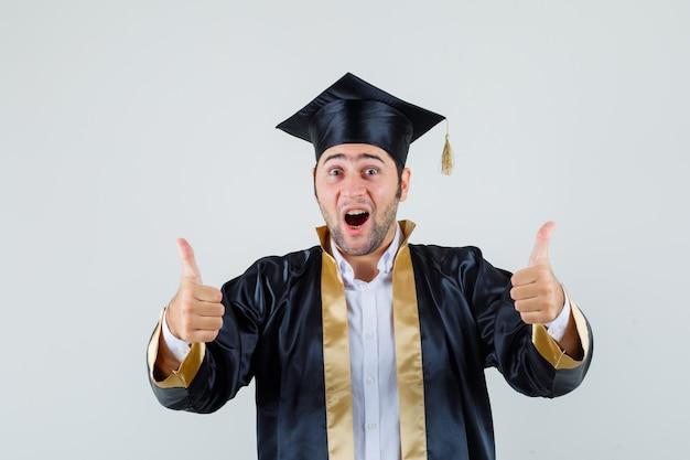 Jonge man dubbele duimen opdagen in afgestudeerde uniform en op zoek vrolijk. vooraanzicht.