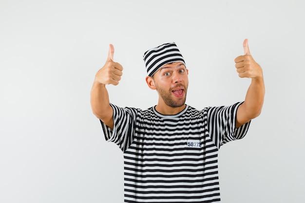 Jonge man dubbele duimen opdagen in gestreepte t-shirt, hoed en vrolijk kijken.